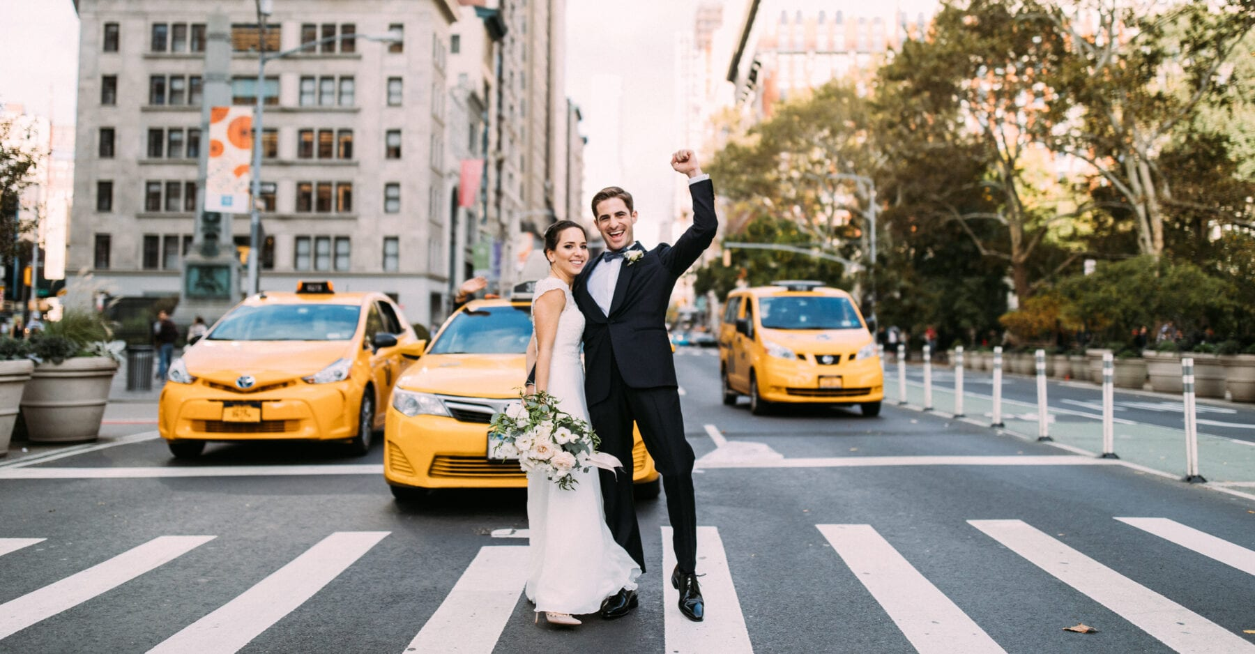 Bride and groom crossing 5th avenue with yellow cabs