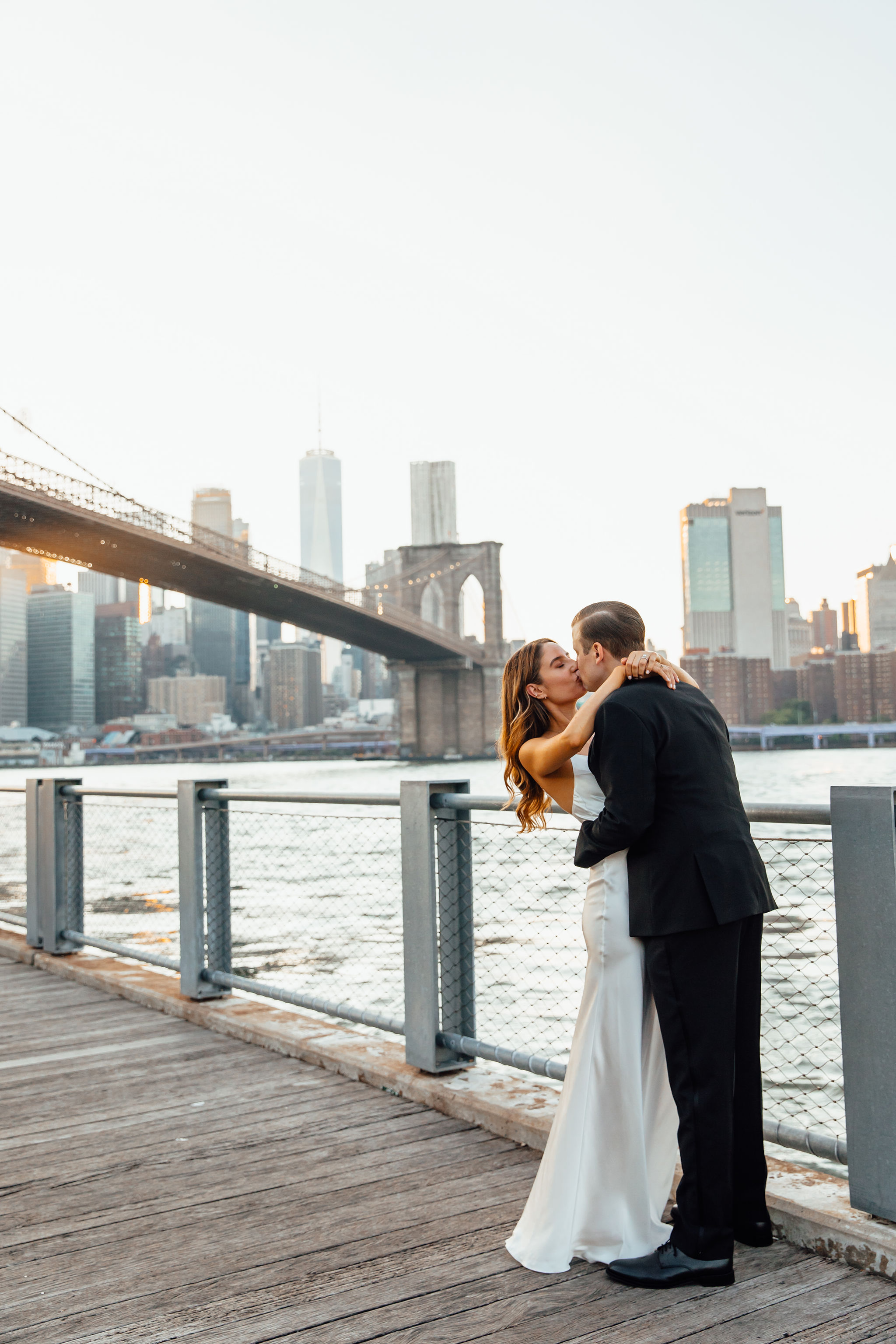 Bride and groom kissing with the Brooklyn Bridge views